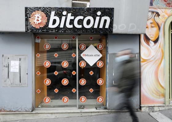 한 남성이 프랑스에 있는 비트코인 디지털 화폐 ATM 가게를 지나가고 있다. 로이터=연합뉴스