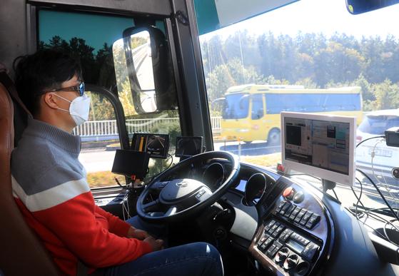 지난해 10월 29일 오전 제주시 애월읍 평화로에 구축된 차세대 지능형 교통체계(C-ITS) 실증사업 자율주행 테스트베드 구간에서 KT 5G 자율주행 버스 운전자가 운전대에서 양손을 놓았지만, 버스가 스스로 주행하고 있다. [연합뉴스]
