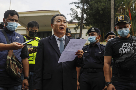 북한이 자국민을 미국에 넘겼다는 이유로 말레이시아와 단교를 선언한 데 이어 지난 21일 말레이시아 대사관을 폐쇄했다. 김유성 말레이시아 주재 북한 대사 대리가 21일 대사관을 떠나기전 말레이시아와 미국 정부를 비난하는 성명을 발표하고 있다. [EPA=연합뉴스]