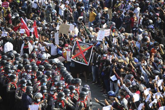 지난달 8일 미얀마의 수도 네피도에서 쿠데타에 항의하는 시민들이 군경과 대치하고 있다. 이들 중 일부가 저항의 의미로 검지·중지·약지를 세우는 '세 손가락 경례'를 하고 있다. 붉은색으로 X표 쳐진 사진의 주인공은 쿠데타의 주역인 민 아웅 흘라잉 장군이다. [AP=연합뉴스]