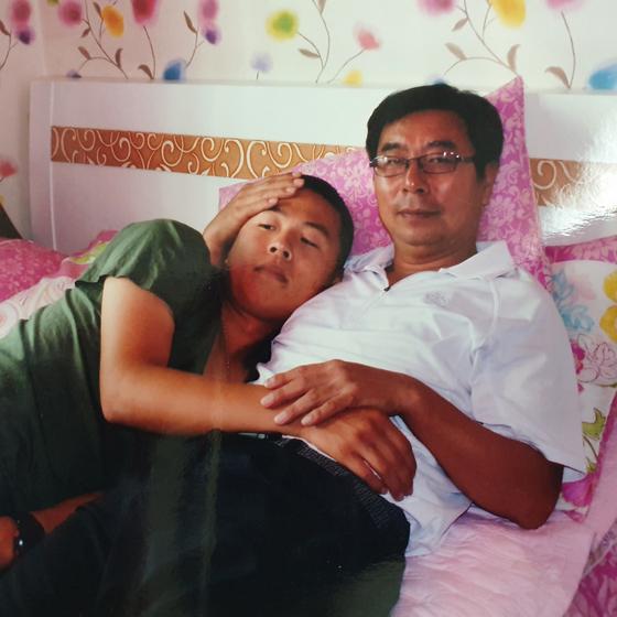 고 문광욱 일병이 2010년 10월 23일 외박 때 숙소 침대에서 아버지 문영조씨 품에 안겨 있다. 한 달 뒤인 11월 23일 북한이 연평도에 기습적으로 포격하던 날 문 일병은 포탄을 나르다 적의 포탄 파편에 맞아 전사했다. 사진 문영조씨