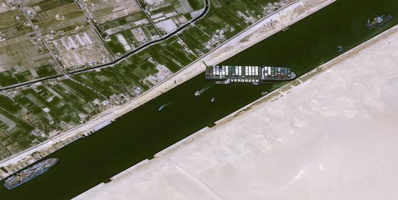 25일(현지시간) 이집트 수에즈운하를 가로막고 있는 에버기븐호를 인양하기 위해 예인선 8대가 투입돼 작업을 벌이고 있다. [AFP=연합뉴스]