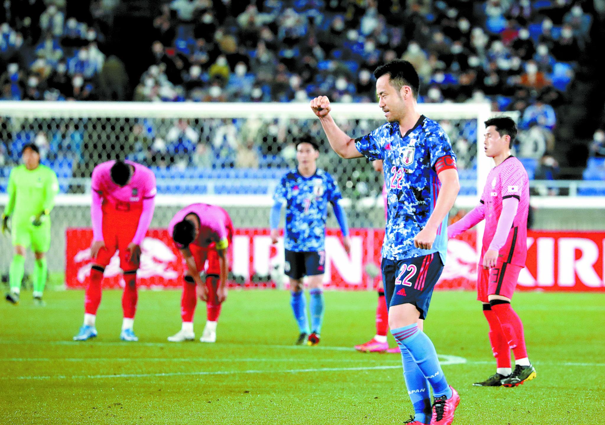 한일전 0-3 완패 직후 아쉬워하는 이동경(오른쪽 첫번째)과 고개 숙인 한국 선수들. 그들 앞에서 주먹을 불끈 쥐며 기뻐하는 일본 수비수 요시다 마야. [연합뉴스]