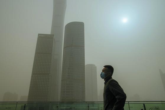 28일(현지시간 ) 중국 베이징에서 마스크를 쓴 남성이 중앙상업지구가 보이는 전망대 앞을 걸어가고 있다. 이날 중국 중앙기상대는 베이징과 허베이 등 15개 성에 황사 황색경보를 발령했다. 베이징 일대의 미세먼지(PM10) 농도 역시 2500㎍/㎥으로 심각한 수준을 기록했다. [EPA=연합뉴스]