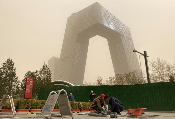 28일 황사로 뒤덮인 중국 베이징시 CCTV 본사 앞에서 공사장 인부들이 작업을 하고 있다. 로이터=연합뉴스