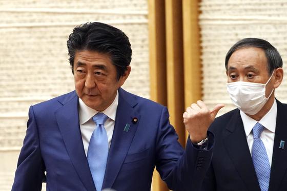 작년 5월 4일 아베 신조 당시 총리가 기자회견을 마치고 퇴장하면서 스가 요시히데 당시 관방장관을 손가락으로 가리키고 있다. [AP=연합뉴스]