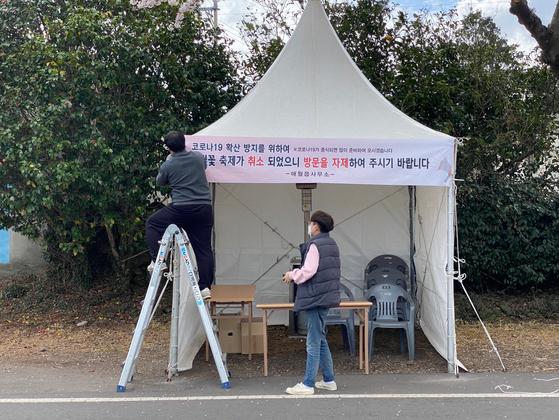 애월읍 관계자들이 24일 장전리 벚꽃 거리에 '방문 자제' 플래카드를 걸고 있다. 최충일 기자