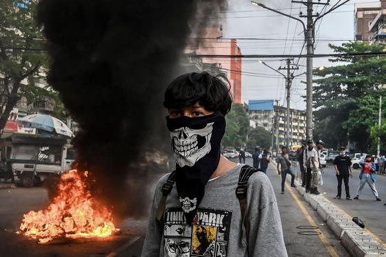 시위대 중 청년 한 명이 복면을 하고 불타는 바리케이드 근처에 서있다. 30일 양곤의 모습이다. AFP=연합뉴스
