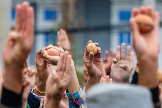 4일(현지시간) 미얀마 샨주의 시위대가 부활절 달걀을 들고 세 손가락 경례를 하며 군부를 규탄했다.[AFP=연합뉴스]