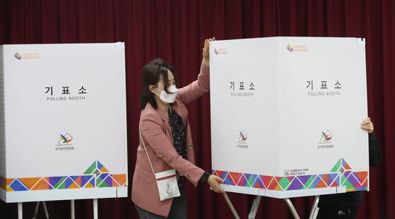 4·7 재보궐선거를 하루 앞둔 6일 서울 중구 장충동주민센터에 마련된 투표소에서 선거관리위원회 관계자들이 투표소 설치 작업을 하고 있다. 뉴스1