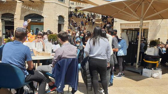이스라엘 식당 앞에 놓인 야외 테이블 자리는 사람들로 꽉차 있고, 식당 앞에는 길게 줄을 서 있다. [사진 이강근씨]