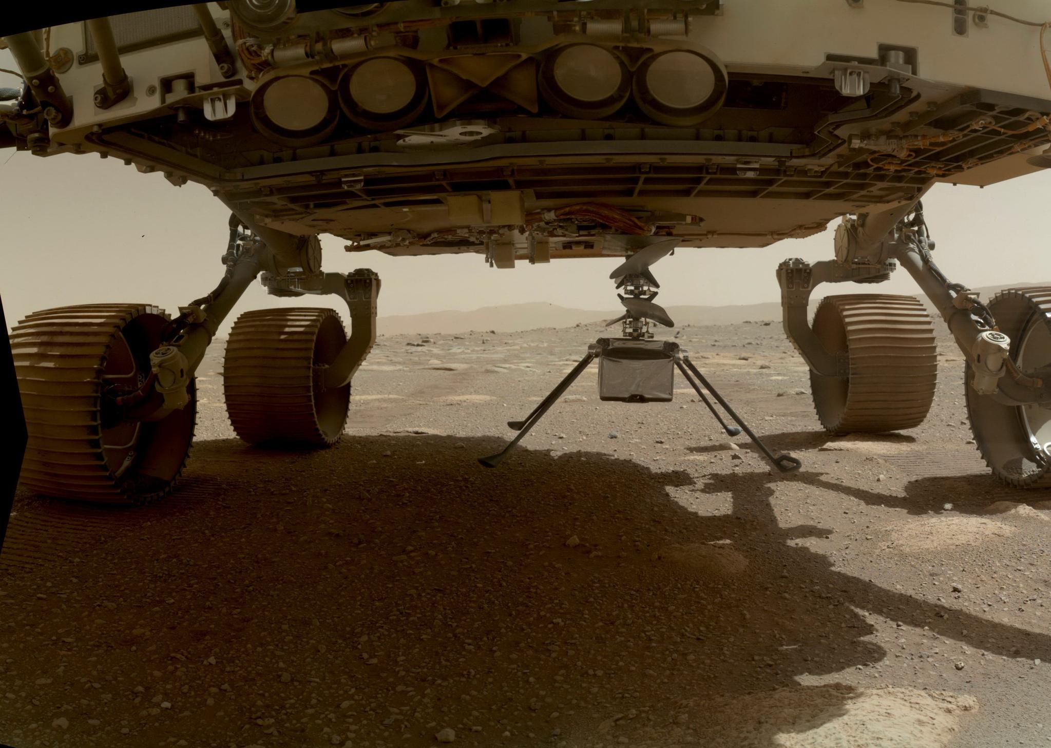소형 헬기 인저뉴어티가 화성 탐사 로버 퍼서비어런스 아래 부착된 보습. 분리되기 전 헬기의 네 발이 펼쳐지고 있다. 지난 3월 30일 촬영하고 4월 6일 미국 항공우주국(NASA)이 제공한 사진이다. AFP=연합뉴스