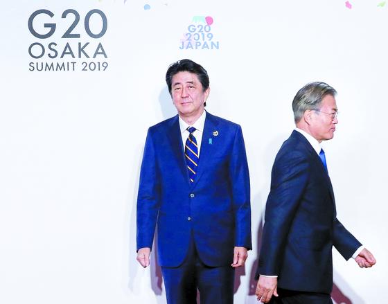 문재인 대통령이 2019년 오사카에서 열린 G20 정상회의 공식환영식에서 의장국인 일본 아베 신조 총리와 악수한 뒤 이동하고 있다. 연합뉴스