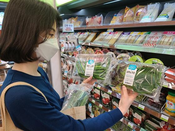 편의점 CU의 지난해 채소 매출이 전년보다 78.3% 증가했다. 사진은 한 CU 매장 내부에서 채소 상품을 들고 있는 모델의 모습. [사진 BGF리테일]