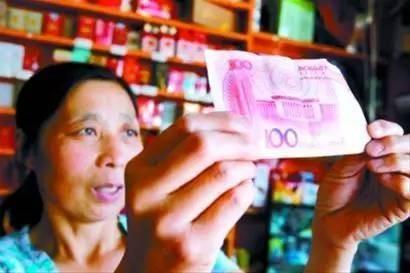 지폐를 들어 위폐 감별을 하는 중국 소상공인 [사진출처=소후닷컴]