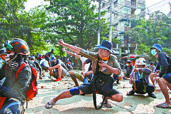 군부 쿠데타에 항의하는 미얀마 시민들이 지난 28일 최대 도시 양곤에서 실탄 사격을 하는 경찰에 새총으로 대응하고 있다. [AP=연합뉴스]