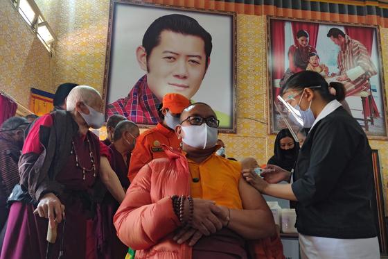 부탄의 지난달 27일 백신 접종 현장. 뒤의 초상화가 '용왕'으로 불리는 부탄 국왕이다. AFP=연합뉴스