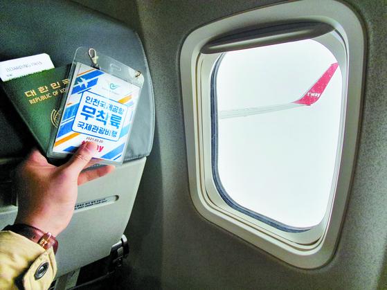 무착륙 국제관광비행을 이용한 한 탑승객이 기내에서 기념사진을 직고 있다. 최승표 기자