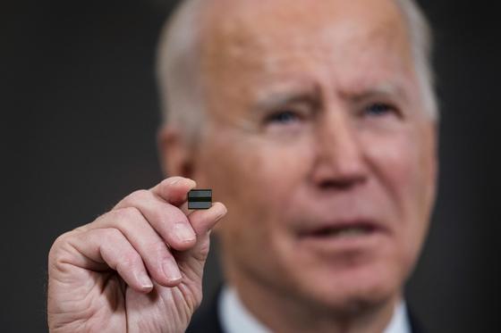 미국의 조 바이든 대통령이 지난 2월 백악관에서 반도체·전기차배터리·희토류 등 주요 물자의 공급망 점검을 지시하는 행정명령에 서명하기 전 반도체 칩을 들어 보이고 있다. [EPA]