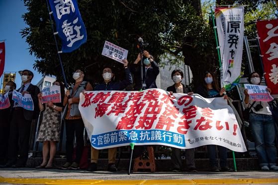 방사능 오염수의 해양배출을 절대로 허옹해서는 안된다는 내용의 펼침막을 들고 시위하는 일본의 활동가들. AFP=연합뉴스