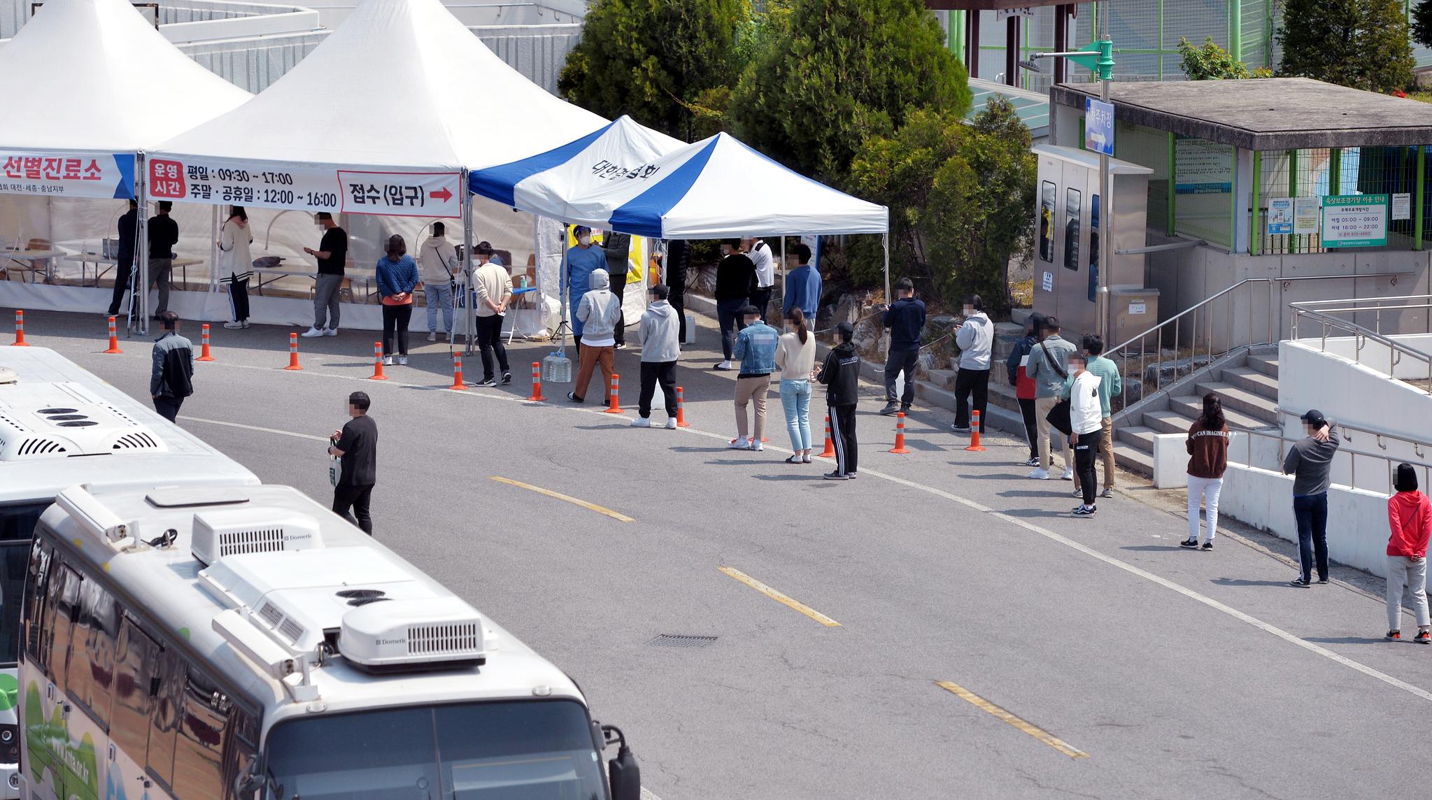 지난 11일 오후 대전 한밭체육관 앞에 마련된 코로나19 선별진료소를 찾은 시민들이 검사를 받기위해 줄 서 차례를 기다리고 있다. 중앙포토