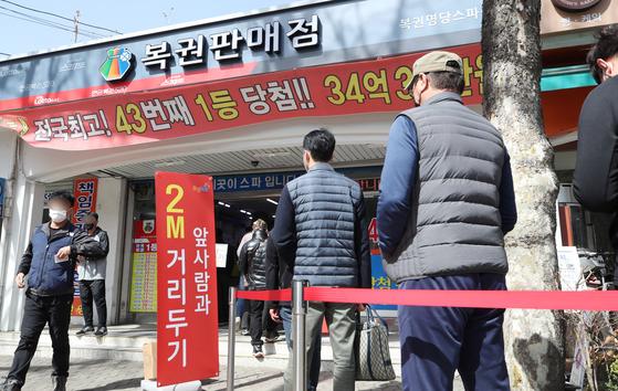지난달 16일 오전 서울 노원구의 복권 판매점 앞에 복권을 사기 위한 시민들이 줄을 서 있다. 뉴스1