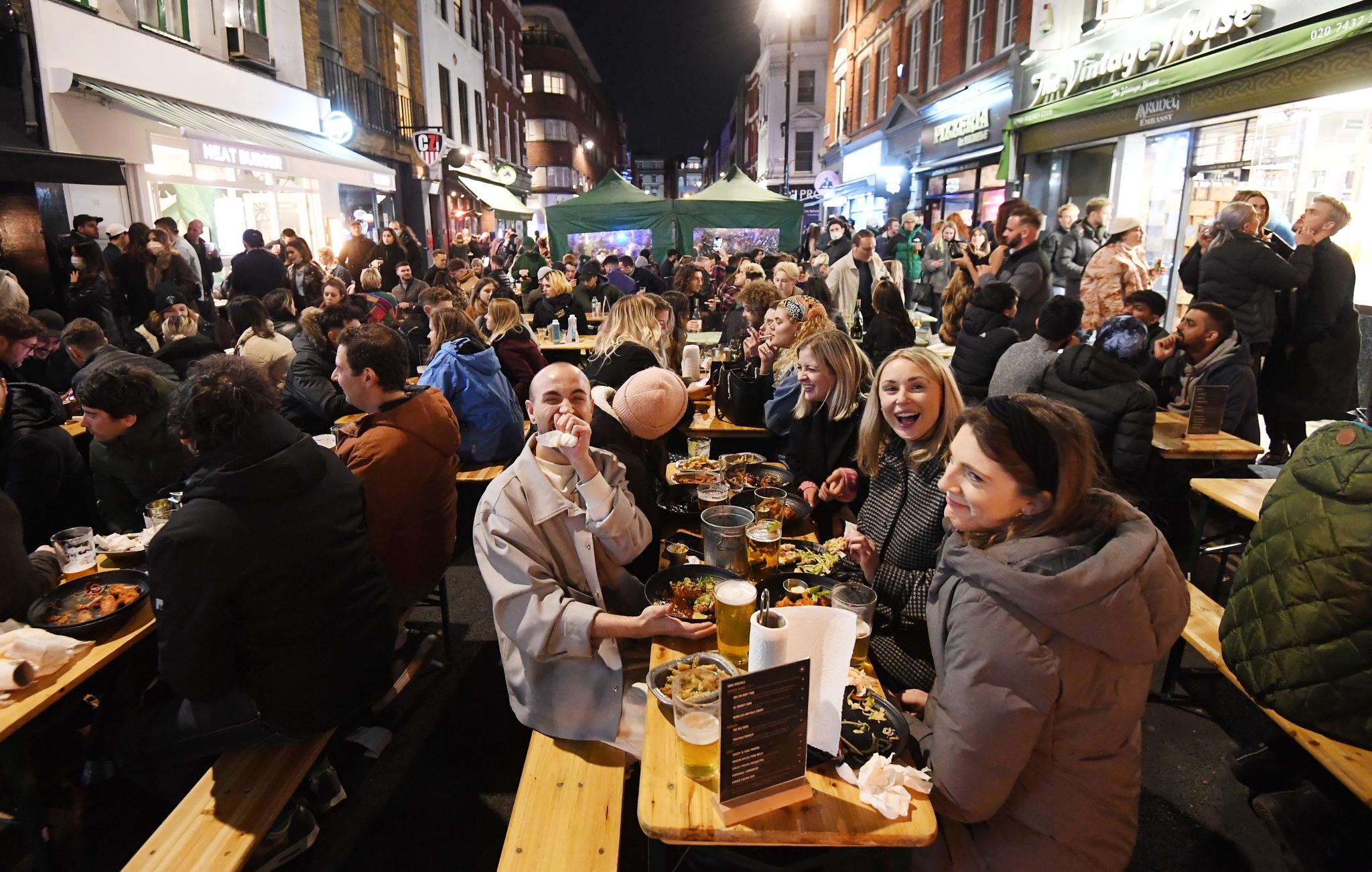 영국 런던 시민들이 12일(현지시간) 소호거리의 야외 식당에서 음식을 먹고 술을 마시고 있다. 영국은 이날부터 코로나 19 방역을 위한 봉쇄조치를 완화해 야외 업소들이 일제히 영업을 재개했다. EPA=연합뉴스