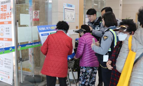 대전서부경찰서 경찰관들이 주민센터에 설치된 '관할 지역 대형지도판'을 보는 주민들에게 순찰이 필요한 지점을 표시하는 방법을 알려주고 있다. [사진 대전서부경찰서]
