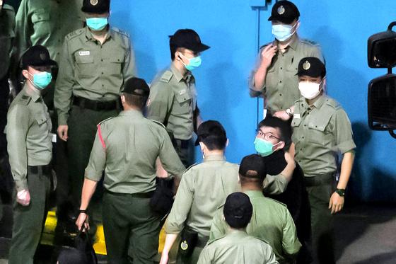 홍콩 민주화 운동가 조슈아 웡이 지난달 2일 교도관의 호위를 받고 있는 모습. 웡은 지난해 12월 불법집회 조직·선동 혐의로 징역 13.5개월을 선고받고 복역 중이다. AP=연합뉴스