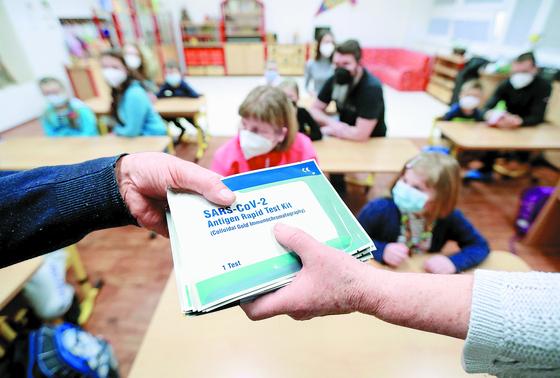 12일(현지시간) 체코의 수도 프라하에서 코로나19 확산이 완화돼 다시 문을 연 한 초등학교에서 직원들이 안티젠 신속검사(항원 검사) 키트를 건네고 있다. [로이터=연합뉴스]