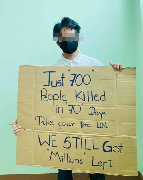 """한 미얀마 청년이 """"70일 동안 700명 밖에 죽지 않았다. 유엔은 천천히 하라. 우린 여전히 수백만명의 (죽을 수도 있는 사람이) 남아있다""""는 문구를 적은 피켓을 들고 있다. 이 사진은 현지 SNS에 빠르게 퍼지고 있다.[SNS 갈무리]"""
