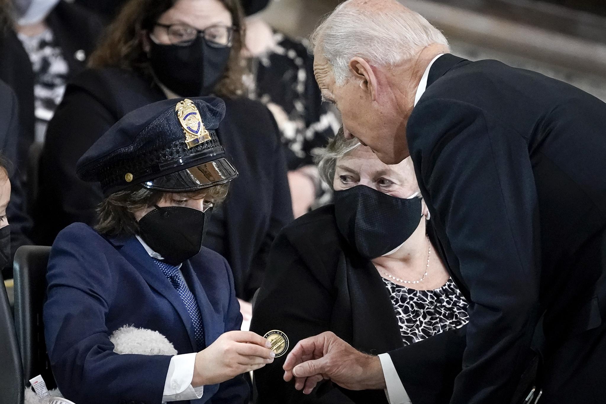 조 바이든 미국 대통령이 13일(현지시각) 연방의사당 로툰다홀에서 열린 윌리엄 에번스 경관 추모식에 참석해 아들 로간에게 백악관 동전을 선물하고 있다. 아들이 쓴 모자는 아버지의 것이다. AP=연합뉴스