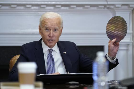 바이든 대통령이 12일 반도체생산업체들과 화상회의에서 반도체를 만드는 웨이퍼를 들고 중국과의 패권경쟁을 강조하고 있다. 연합뉴스