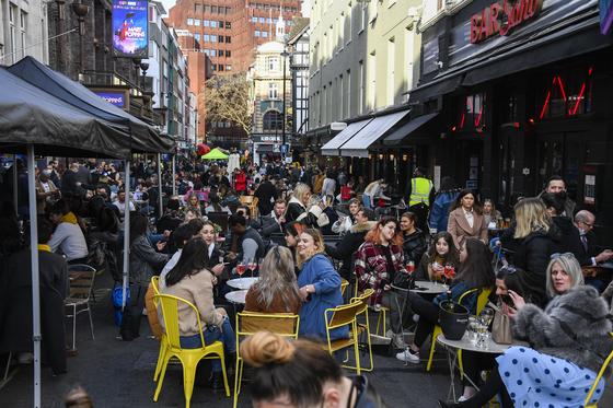 영국 잉글랜드 당국이 12일 0시를 기점으로 코로나19 방역을 완화해 야외 식당·술집과 상점·미용실·체육관·놀이공원의 영업을 허용하자 이날 런던의 업소들이 손님으로 붐비고 있다. [AP=연합뉴스]