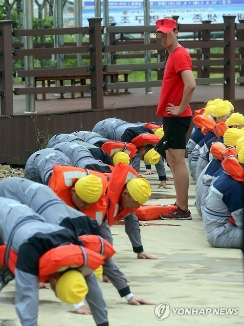 한국해양대 해사대학생들이 2015년 8월 24일 해상 생존업 훈련을 하던 중 얼차려를 받는 모습.[연합뉴스]
