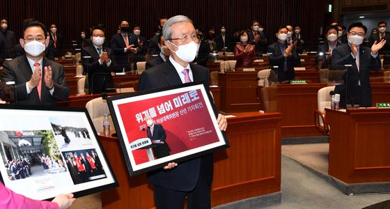 김종인 전 국민의힘 비상대책위원장은 지난 8일 퇴임했다. 이날 국회에서 열린 의원총회에서 당 홍보국으로부터 기념액자를 받고 있다. 오종택 기자
