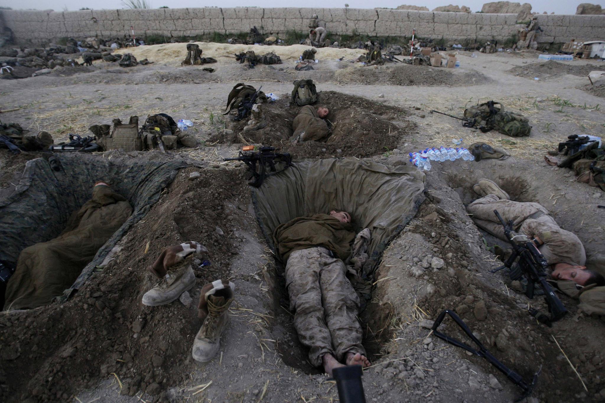 시신 같지만 미군이 기지 내의 전투 참호(fighting holes)에서 휴식을 취하는 모습이다. 2009년 7월 8일 아프간 헬만드 주 전투 현장이다. AP=연합뉴스