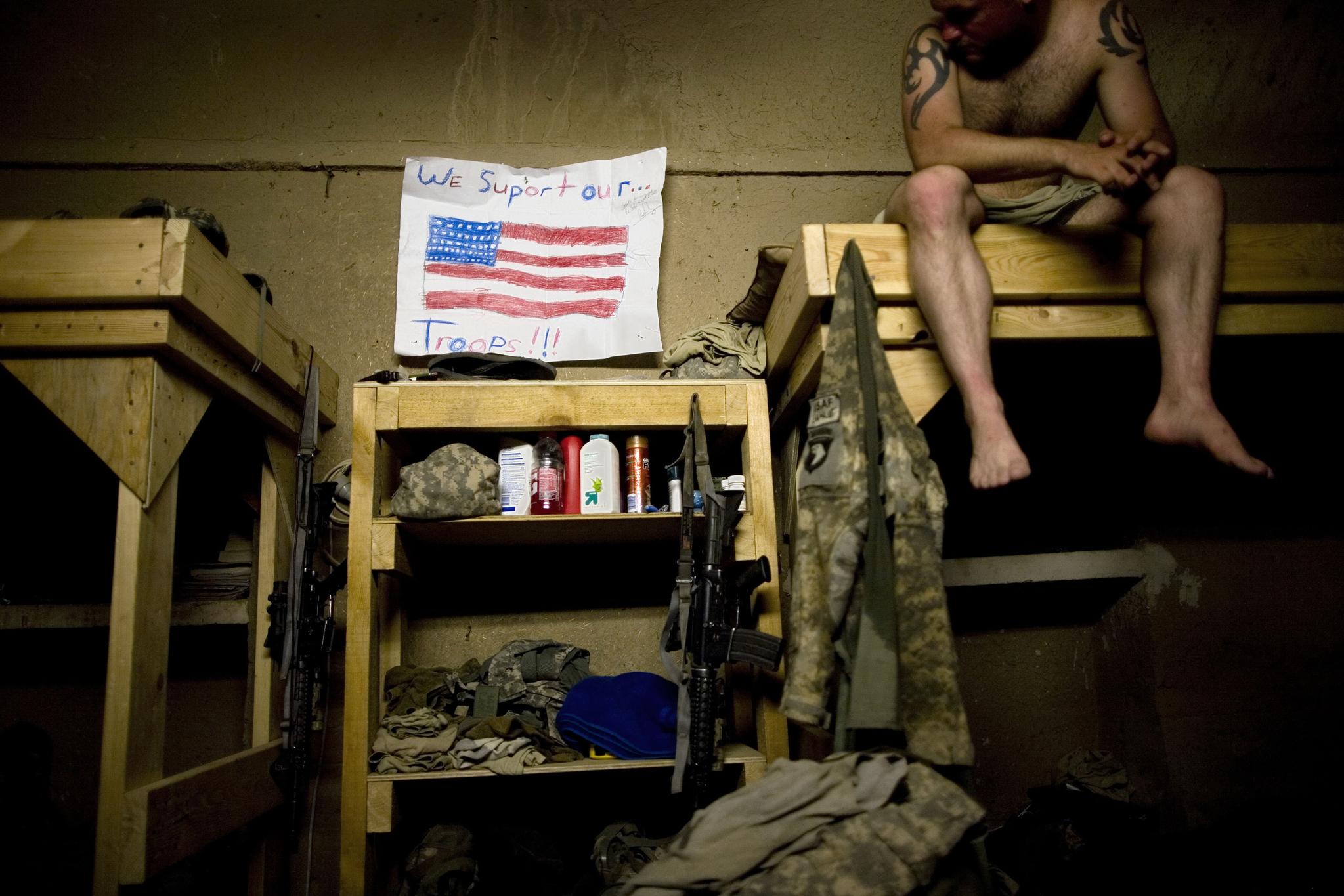 """2010년 7월 29일 미국 텍사스 주 호클리 출신의 미군 댈러스 퍼디가 아프간 칸다하르의 내무반에서 휴식하고 있다. 벽에 미국 국기가 걸려 있다. 글씨는 """"우리는 미군을 지원한다(We support our troops!!!)"""". AP=연합뉴스"""
