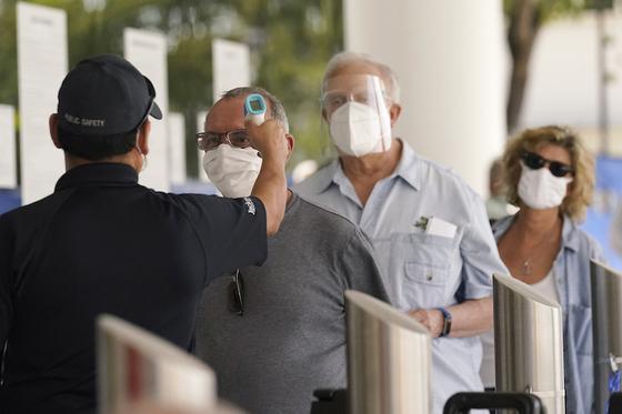 지난 2월 미국 플로리다 주 마이애미의 한 보건소에서 65세 이상인 사람들이 2차 코로나19 예방주사를 맞기 전에 체온을 측정하고 있다. AP=뉴시스