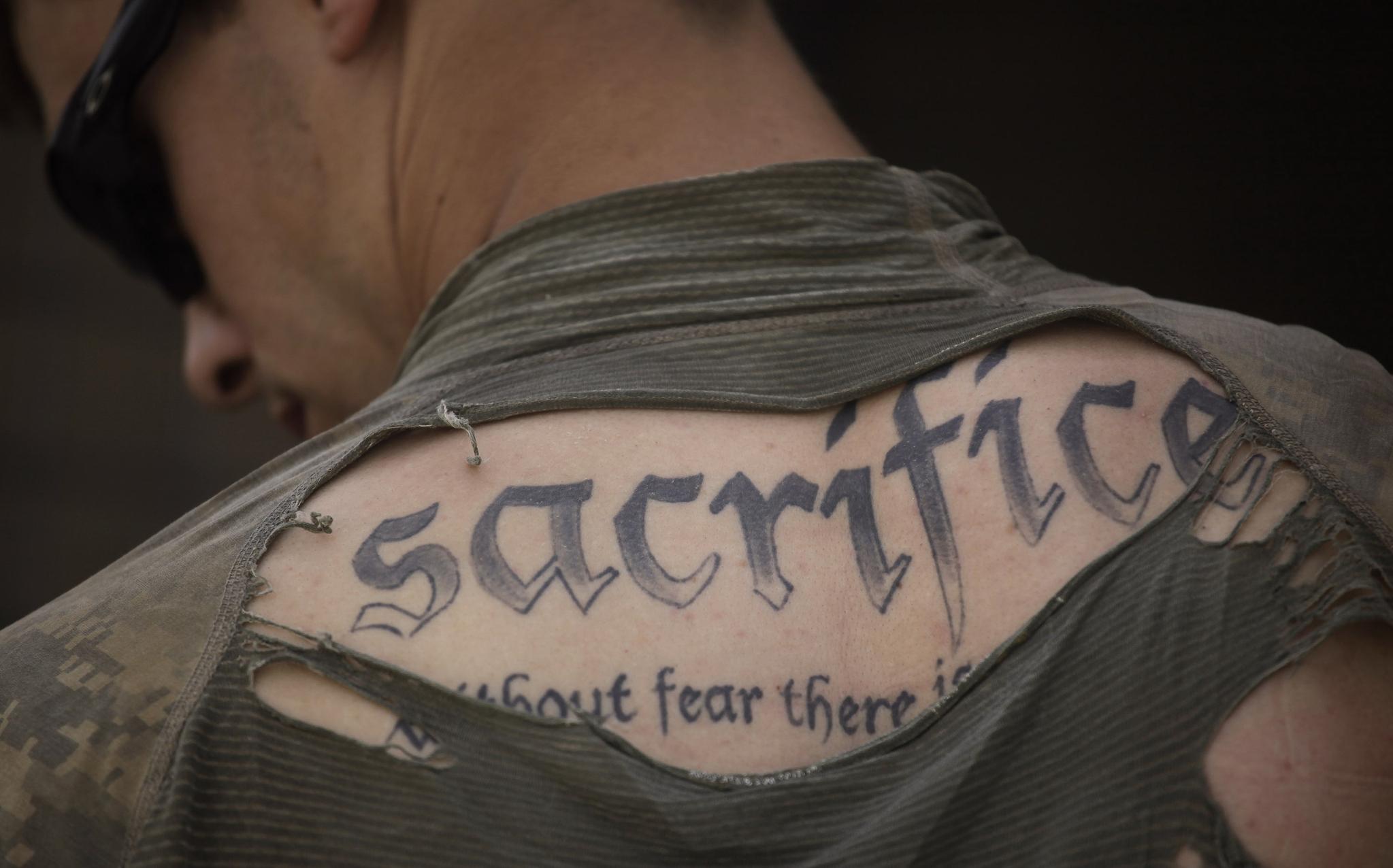 """2010년 5월 8일 아프간 칸다하르 주에서 도보 순찰을 마치고 돌아온 미국 뉴욕 로체스트 출신 육군 병장 제임스 윌키스의 등에 새겨진 타투. """"희생. 두려움이 없으면 용기도 없다(Sacrifice. Without fear there is no courage)""""고 썼다. AP=연합뉴스"""