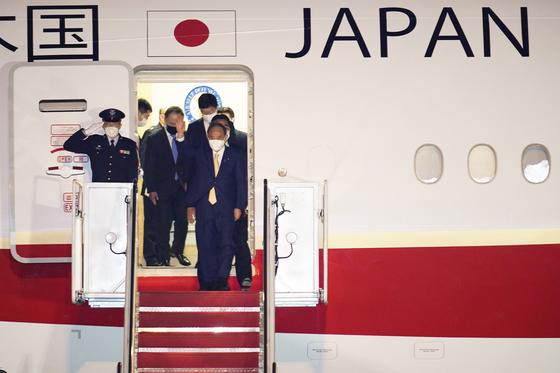 스가 요시히데 일본 총리가 15일(현지시간) 조 바이든 미국 대통령과 회담을 하기 위해 미국 앤드루스 공항에 도착해 비행기에서 내리고 있다. [AP=연합뉴스]