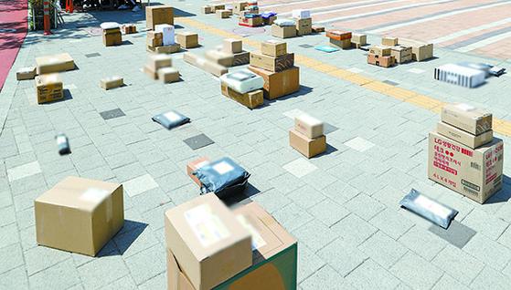 택배 차량의 단지 내 지상 도로 진입을 막은 서울 강동구의 한 아파트 앞에 15일 오후 택배 물품들이 남아 있다. [뉴시스]