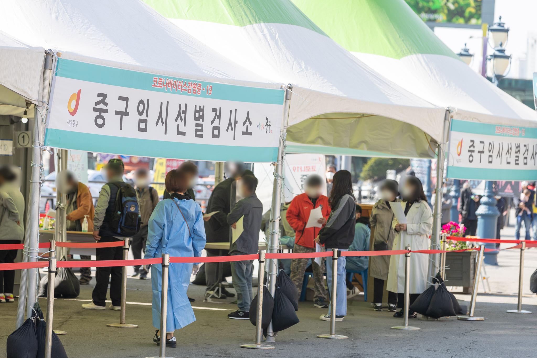 신종 코로나바이러스 감염증(코로나19) 신규 확진자가 600명대 발생한 18일 오전 서울 중구 서울역광장에 마련된 임시선별진료소를 찾은 시민들이 검사를 받기 위해 줄을 서 있다. 뉴스1