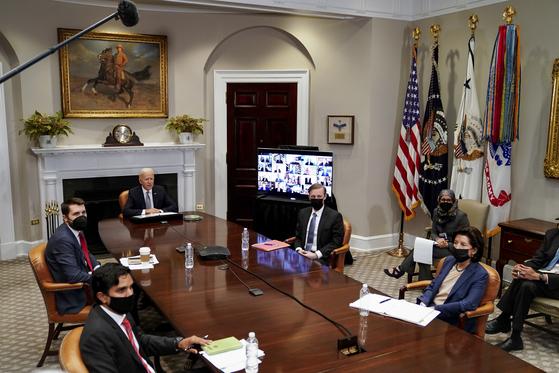 조 바이든 미국 대통령(가운데)이 지난 12일(현지시간) 워싱턴 백악관 루스벨트룸에서 '반도체 서밋' 화상회의에 참석해 발언하고 있다. 책상 왼쪽에 반도체 웨이퍼가 놓였다. [EPA]