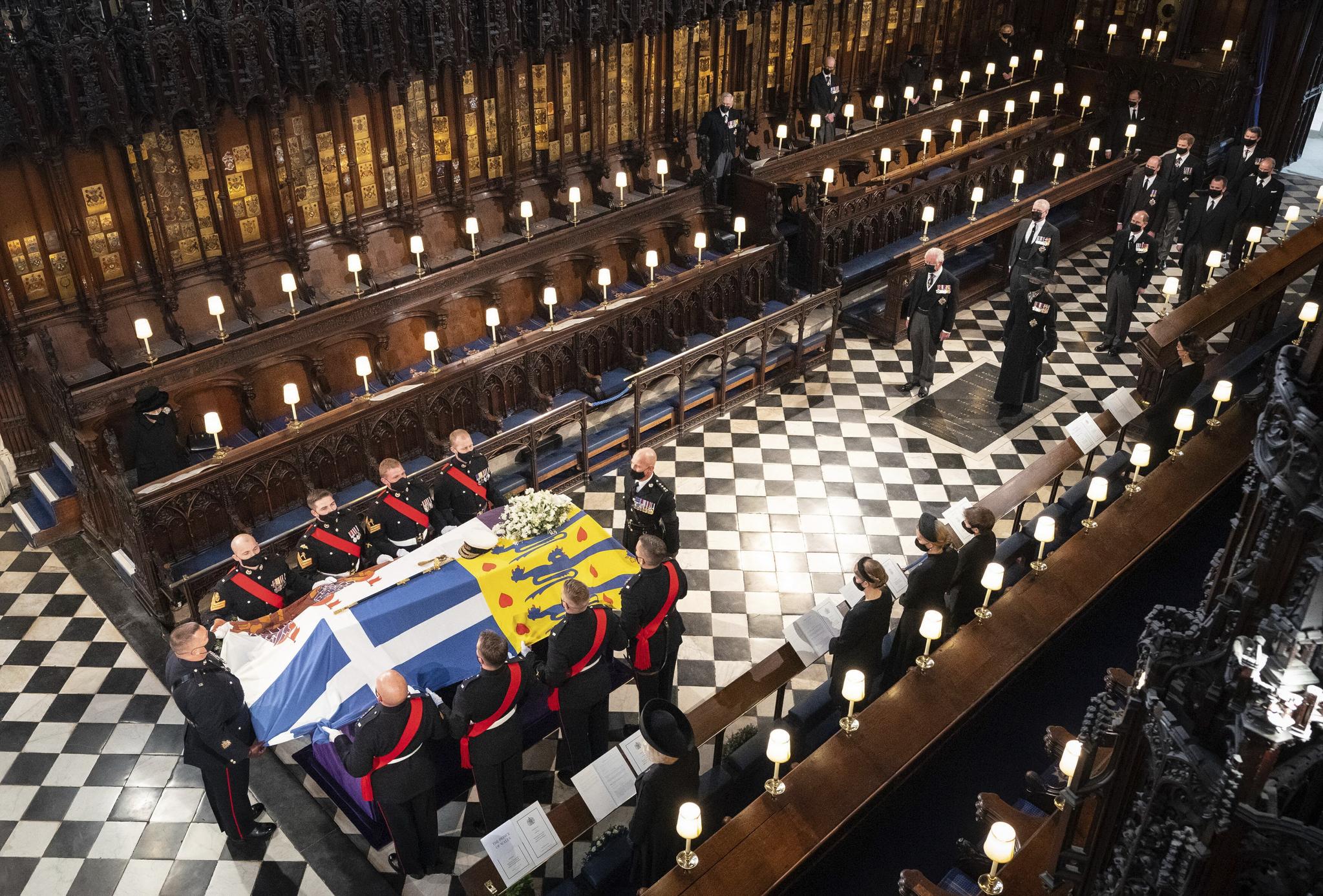 엘리자베스 2세 영국여왕(왼쪽 위)이 17일 윈저성 성조지 예배당에서 열린 부군 필립공 장례식에 참석해 운구 행렬이 장례식장에 들어오는 모습을 바라보고 있다. 지난 9일 99세를 일기로 타계한 필립공은 73년간 여왕의 곁을 지켰다. AP=연합뉴스