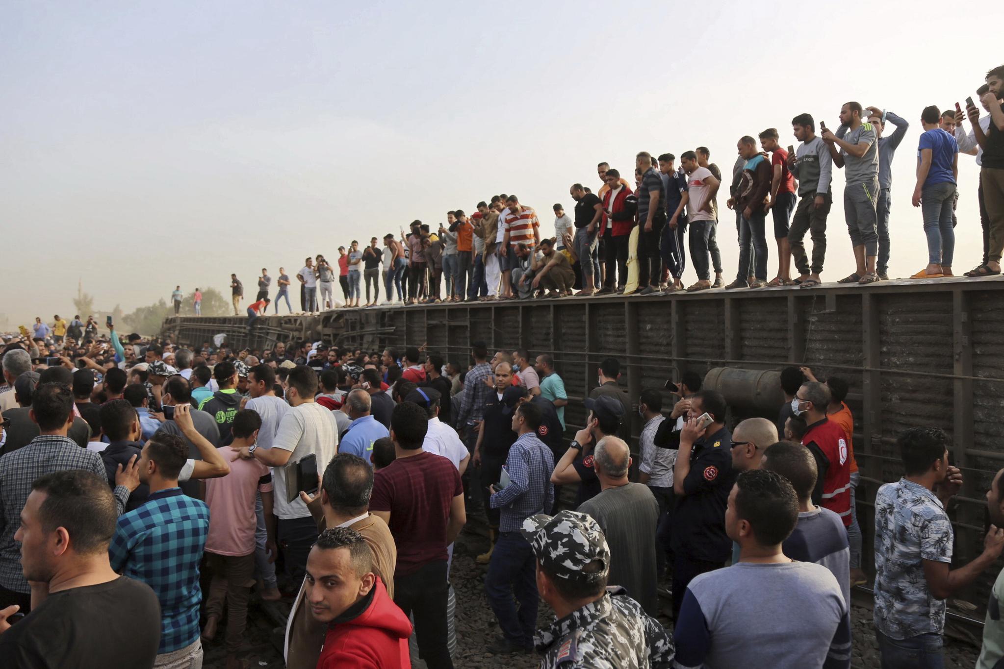 최소 8량의 객차가 탈선한 이집트 열차 사고 현장. 주민들이 옆으로 누운 객차 위에 올라가 일부는 휴대폰으로 사진을 촬영하고 있다. AP=연합뉴스