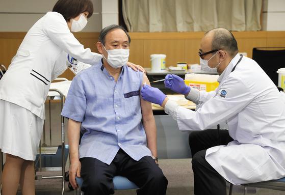 스가 요시히데 일본 총리가 지난달 16일 도쿄 신주쿠의 한 의료기관에서 코로나19 백신을 맞고 있다. [교도=연합뉴스]