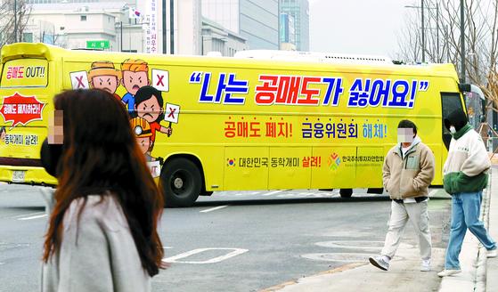 개인투자자 모임인 한국주식투자연합회(한투연)가 2월 서울 세종로에서 공매도 반대 운동을 위해 '공매도 폐지', '금융위원회 해체' 등의 문구를 부착한 버스를 운행하고 있다. 연합뉴스