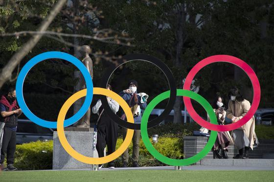 지난달 19일 일본 도쿄 올림픽 박물관에 설치된 오륜 조형물 인근에서 시민들이 사진을 찍고 있다. [AP=연합뉴스]