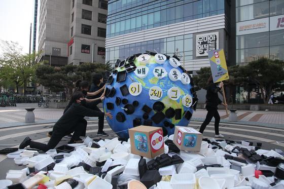 서울 우아한 형제들(배달의 민족) 사옥 앞에 플라스틱에 뒤덮인 지구 형상과 일회용 플라스틱 배달 용기가 쌓여 있다. 녹색연합